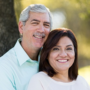 Husband and wife smiling after dental crown restoration