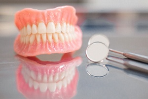 Upper and lower dentures next to dental mirrors