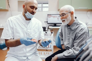 Dentist talking with patient, explaining how dentures work