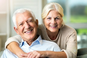 Happy senior couple at home, enjoying benefits of dentures