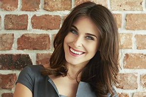 Woman with porcelain veneers smiling against brick wall