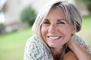 Woman smiling outside after restorative dentistry