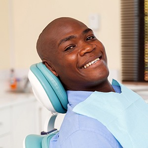 Man laying back showing off smile after root canal therapy