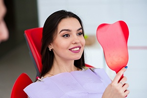 Woman checking smile in red mirror after root canal therapy